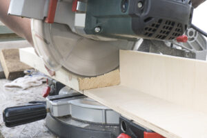 Close-up Of A Carpenter Working With A Miter Saw To Cut A Piece