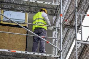 Plastering the wall outdoor on scaffold at building under construction